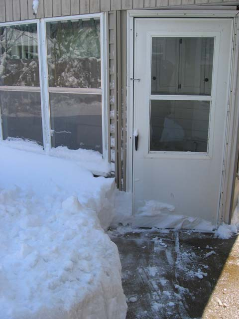 Snow up against the back porch